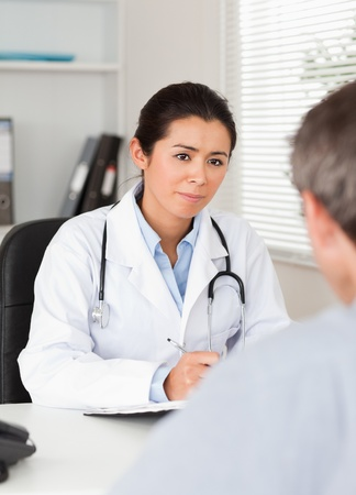 carefully: Pretty female doctor listening carefully to a patient in her office