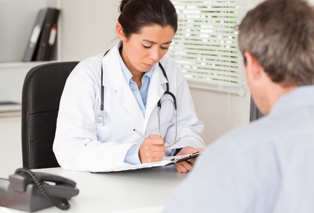 Pretty female doctor consulting the patients medical analysis in her office photo