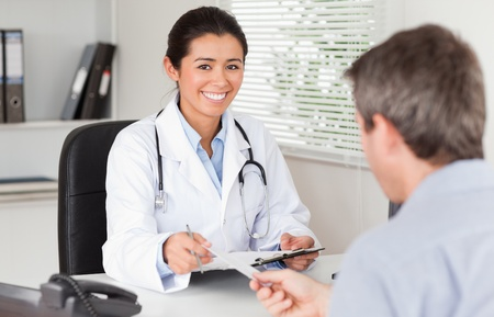 Patient giving his attractive female doctor a piece of paper in her office photo