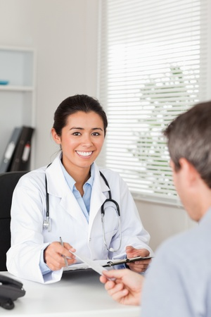 Patient giving his good looking female doctor a piece of paper in her office photo