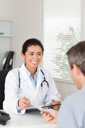 Patient giving his pretty female doctor a piece of paper in her office photo