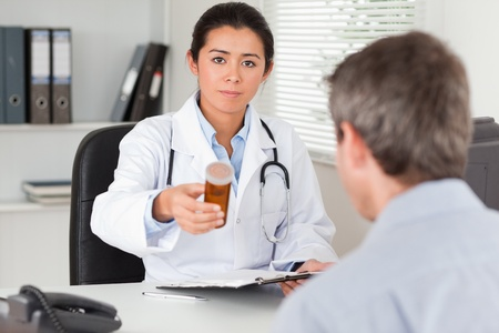 Beautiful female doctor showing a box of pills to the camera in her office photo