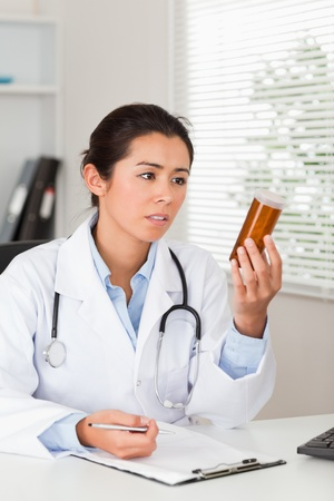 Beautiful worried doctor holding a box of pills in her office photo