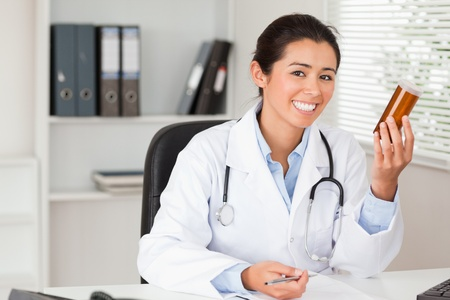 Attractive smiling doctor holding a box of pills in her office photo