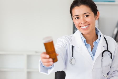 Pretty smiling doctor holding a box of pills in her office photo