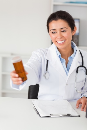 Lovely smiling doctor holding a box of pills while sitting in her office photo