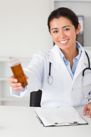 Beautiful smiling doctor holding a box of pills while sitting in her office photo