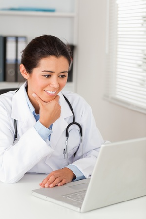 Beautiful female doctor working with her laptop while sitting in her office photo