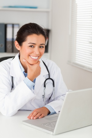 Beautiful female doctor working with her laptop while posing in her office photo