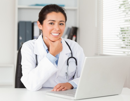 Attractive female doctor working with her laptop while posing in her office photo