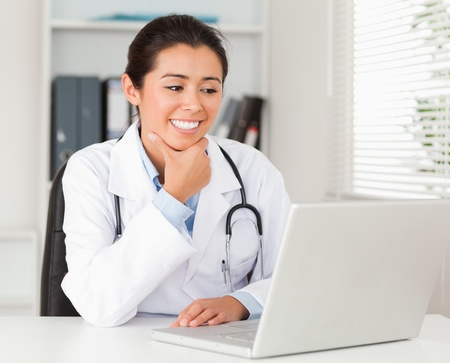 Attractive female doctor working with her laptop while sitting in her office photo