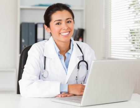 medico computer: Buona medico che cerca lavoro femminile con il suo computer portatile mentre posa nel suo ufficio