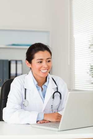 Lovely female doctor working with her laptop while sitting in her office photo