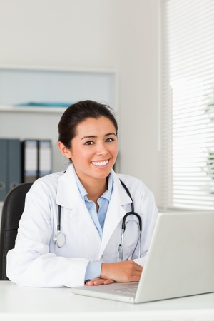 Lovely female doctor working with her laptop while posing in her office photo