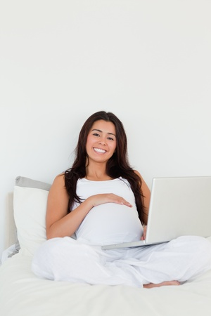 Good looking pregnant woman relaxing with her laptop while lying on a bed at home photo