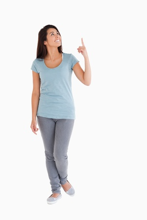 look pleased: Attractive woman showing a copy space with her finger while standing against a white background Stock Photo