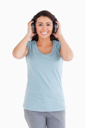 Attractive woman using her headphones while posing against a white background photo
