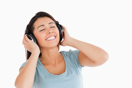 Lovely woman using her headphones while standing against a white background photo