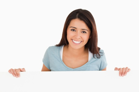 Beautiful woman holding a  board while standing against a white background Stock Photo - 11197951