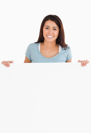 Attractive woman holding a  board while standing against a white background Stock Photo - 11197782