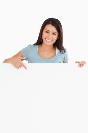 Beautiful woman pointing at a board while standing against a white background photo