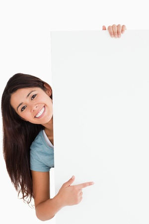 Good looking woman pointing at a board while standing against a white background Stock Photo - 11198327