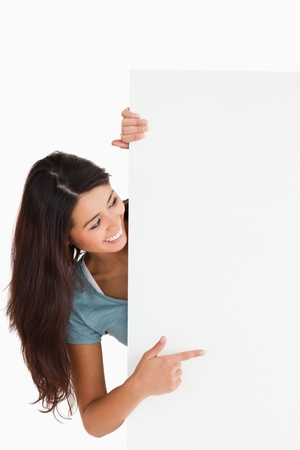 Pretty woman pointing at a board while standing against a white background photo