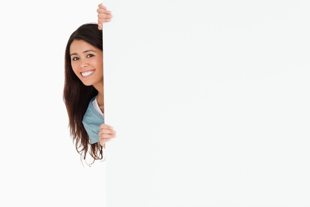 Beautiful woman hidding behind a board while standing against a white background photo