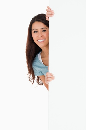Good looking woman hidding behind a board while standing against a white background Stock Photo - 11197946