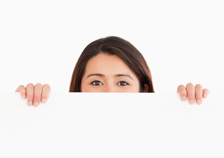 Lovely woman hidding behind a board while standing against a white background Stock Photo - 11197657