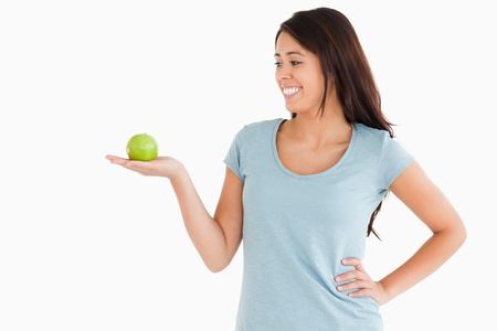 Beautiful woman holding a green apple while standing against a white background Stock Photo - 11198422