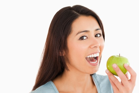 Lovely woman eating a green apple while standing against a white background Stock Photo - 11201407