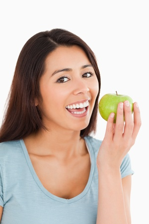 Beautiful woman eating a green apple while standing against a white background Stock Photo - 11202350