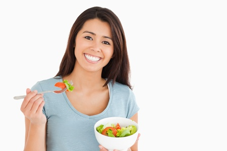 Beautiful woman eating a bowl of salad while standing against a white background photo