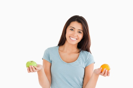 Good looking woman holding an apple and an orange while standing against a white background photo