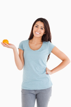 Good looking woman holding an orange while standing against a white background photo