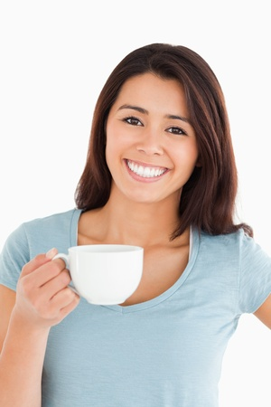 Beautiful woman enjoying a cup of coffee while standing against a white background photo