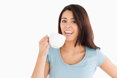 Attractive woman enjoying a cup of coffee while standing against a white background photo