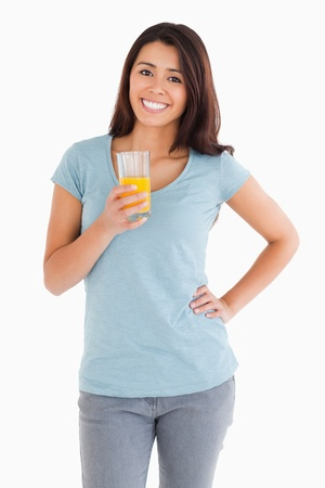 Gorgeous woman holding a glass of orange juice while standing against a white background photo