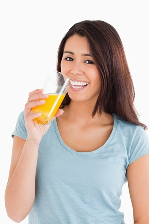 Beautiful woman drinking a glass of orange juice while standing against a white background photo