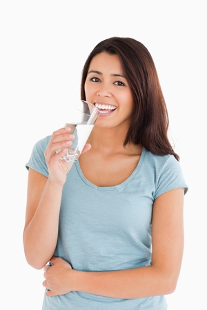 Gorgeous woman drinking a glass of water while standing against a white background photo