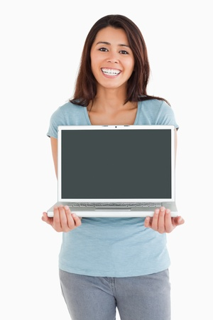 Good looking woman posing with her laptop while standing against a white background photo