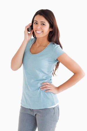 Gorgeous woman on the phone standing against a white background photo