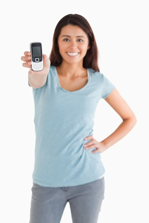 Beautiful woman showing her mobile phone while standing against a white background photo