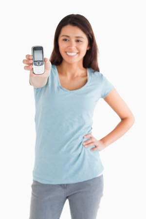 Attractive woman showing her mobile phone while standing against a white background photo
