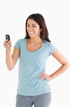 Attractive woman looking at her mobile phone while standing against a white background photo