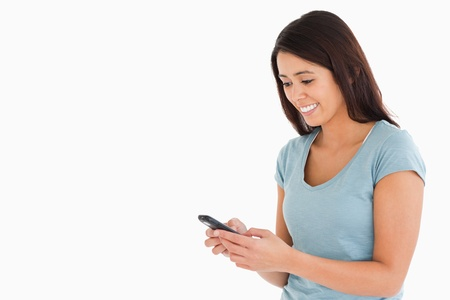 Attractive woman writing a text on her mobile phone while standing against a white background photo