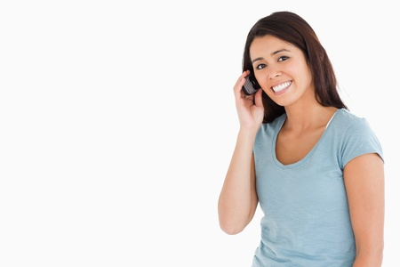 Attractive woman on the phone standing against a white background photo