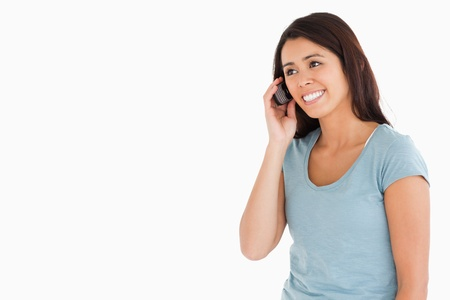 Beautiful woman on the phone standing against a white background photo