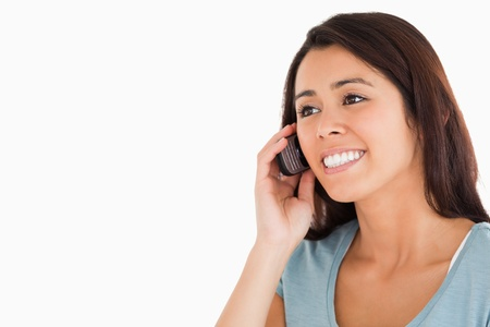 Portrait of a beautiful woman on the phone standing against a white background photo